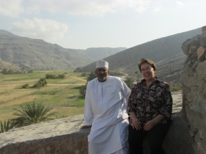 Mohammad and me sitting on a stone wall next to a house