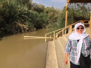 standing on the Jordan side of the Jordan River (Israel is just on the other side!)