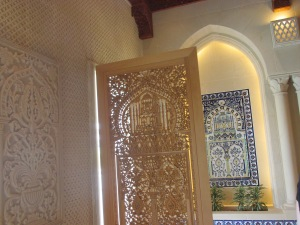 hand-carved wooden screen panel that replicates the tiled panel on the wall behind it.