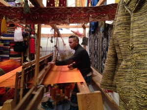 Weaver with a hand pulled flying shuttle and foot operated treadle.
