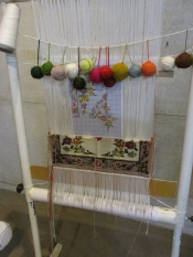 This shows 1/4 of the pattern (on the graph paper), the colored yarns, and part of the rug.