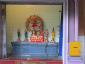 Many small shrines line the walls around the inside of the temple and people leave gifts of food and lotus blossoms in front as they pray.